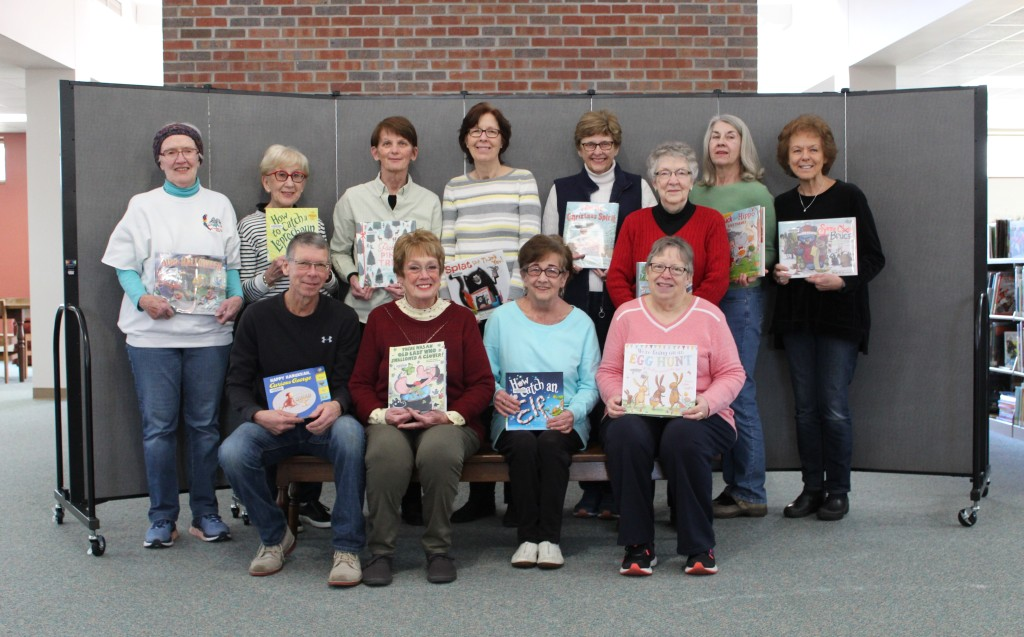 Members of the Odell Public Library Friends hold up updated holiday books for the Children's Department. They also helped the library purchase the portable room divider behind them.
